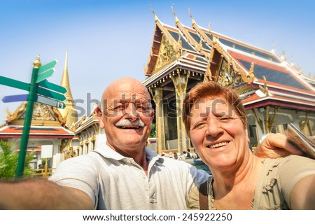 Senior happy couple taking a selfie at Grand Palace temples in Bangkok - Thailand adventure travel to asian destinations - Concept of active elderly and fun around the world with new technologies - stock photo