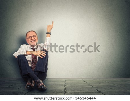 Senior happy man sitting on floor with legs crossed and pointing up. Full length studio shot isolated on gray wall background. - stock photo