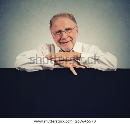 Senior happy man with blank space black banner isolated on gray wall background