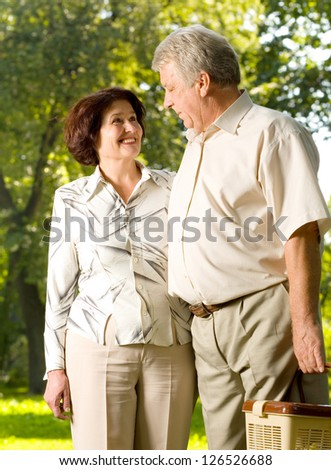 Senior happy smiling cheerful couple walking in park, looking at each other - stock photo