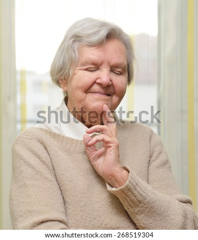 Senior happy woman in her home with window on background. MANY OTHER PHOTOS FROM THIS SERIES IN MY PORTFOLIO.
