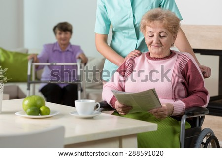 Senior happy woman on wheelchair reading the morning newspaper - stock photo