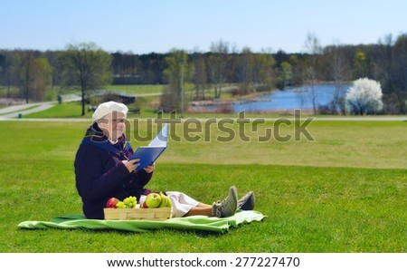 Senior happy woman sitting on a blanket on glade in the park. She is reading book. Healthy outdoor activities. Happy and smiling. - stock photo