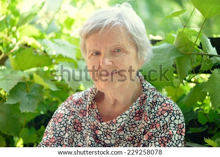 Senior happy woman smiling in garden. - stock photo