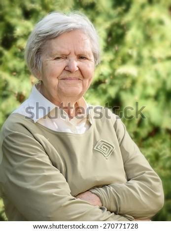 Senior happy woman smiling in garden. - stock photo