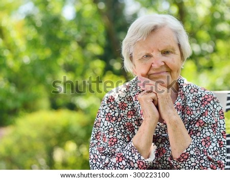 Senior happy woman smiling in garden.MANY OTHER PHOTOS FROM THIS SERIES IN MY PORTFOLIO. - stock photo