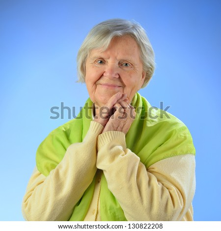 Senior happy woman with grey hairs against blue background. MANY OTHER PHOTOS FROM THIS SERIES IN MY PORTFOLIO. - stock photo