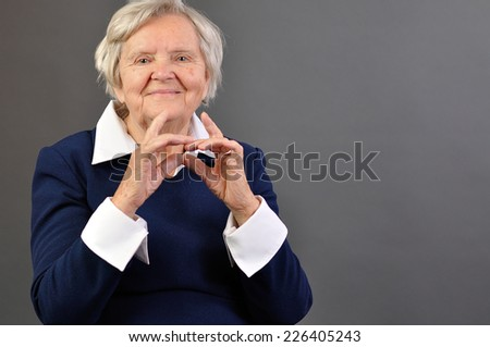 Senior happy woman with grey hairs against grey background.