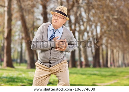 Senior having a cardiac arrest outdoors, in the park - stock photo