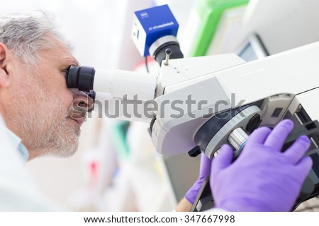 Senior head scientist  microscoping in the life science research laboratory ( diagnostics, biochemistry, pharmacy, genetics, forensics, microbiology, pharmacogenetics ...) - stock photo