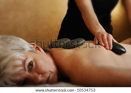 Senior Health and Fitness Spa Hot Mineral Stone Massage Treatment - stock photo
