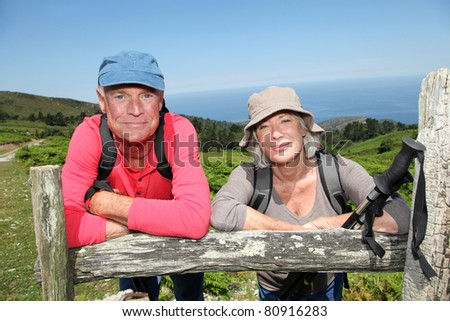 Senior hikers standing by a fence - stock photo
