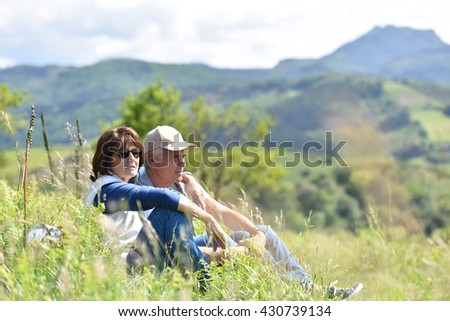 Senior hiking couple sitting in grass on journey