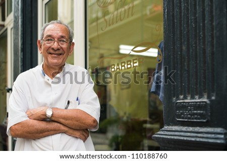 senior hispanic barber in old fashion barber's shop, posing and looking at camera with arms crossed near shop window - stock photo