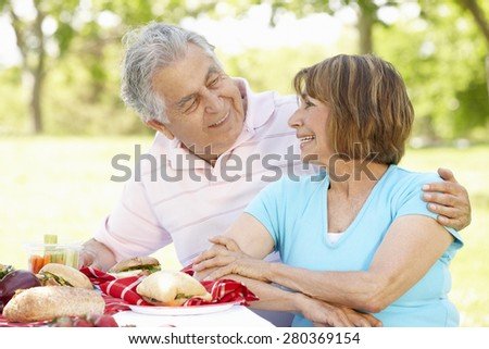 Senior Hispanic Couple Enjoying Picnic In Park