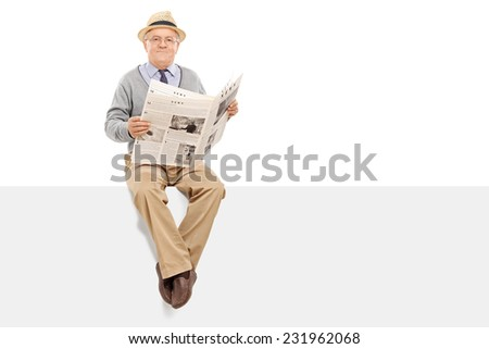 Senior holding a newspaper seated on a panel isolated on white background - stock photo