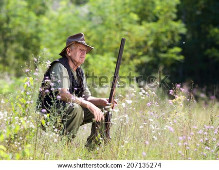 Senior hunter with shotgun sitting on meadow - stock photo