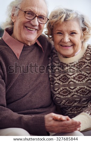 Senior husband and wife looking at camera with smiles - stock photo