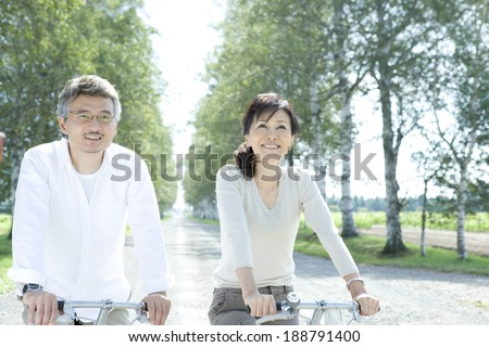 senior husband and wife riding on bicycle - stock photo