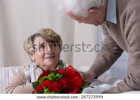 Senior husband giving his wife anniversary gift - stock photo
