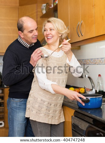 Senior husband helping happy wife to cook indoors - stock photo
