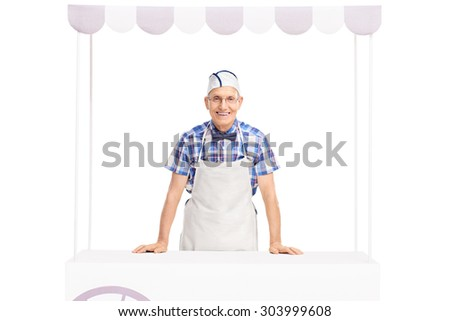 Senior ice cream seller with a white cap and apron standing behind an ice cream stand and looking at the camera isolated on white background - stock photo