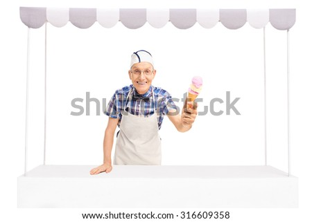 Senior ice cream vendor standing behind a stall and giving an ice cream towards the camera isolated on white background - stock photo
