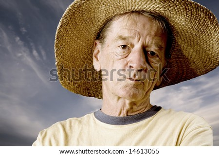 Senior in a straw hat in front of cloudy sky