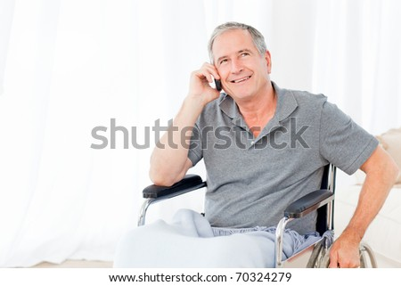 Senior in his wheelchair phoning at home - stock photo