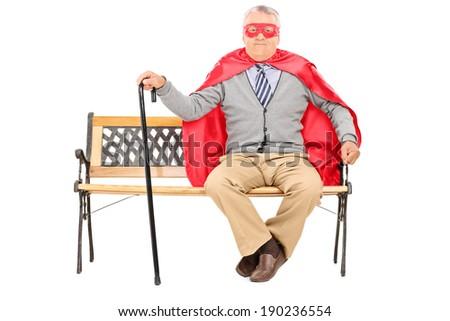 Senior in superhero costume sitting on a bench isolated on white background - stock photo