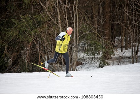 senior in winter on snow with skis cross-country skiing - stock photo