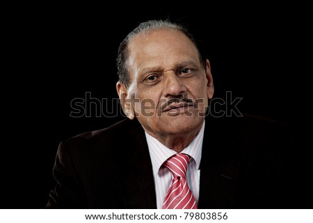Senior indian man in business suit, horizontal portrait on black background - stock photo