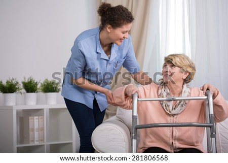 Senior injured woman with walker trying to stand up - stock photo