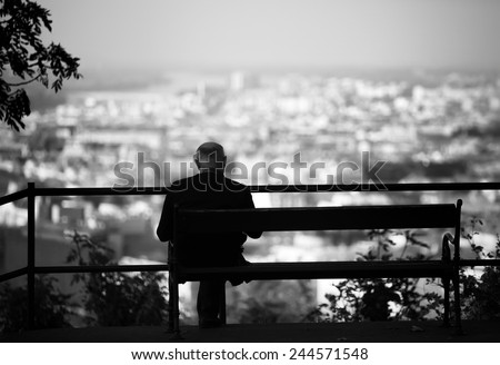 Senior is sitting alone on the bench looking at city at evening. A lonely old man sitting on a bench in a park.Elderly gentleman on park bench in contemplation,black and white photo - stock photo