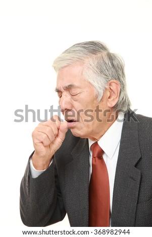 senior Japanese businessman coughing - stock photo