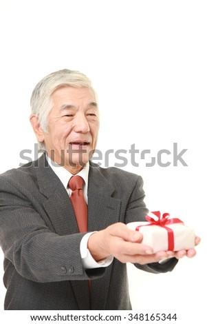 senior Japanese businessman offering a gift  - stock photo