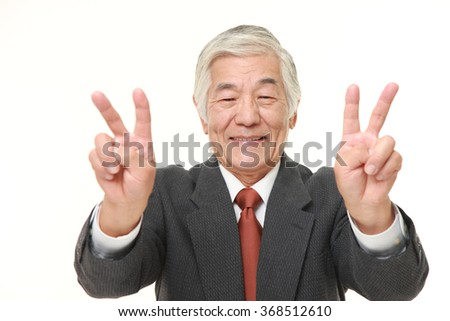 senior Japanese businessman showing double victory sign  - stock photo