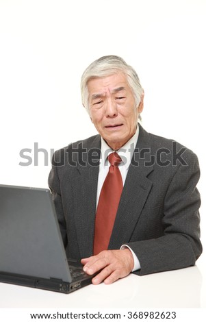 senior Japanese businessman using computer looking confused