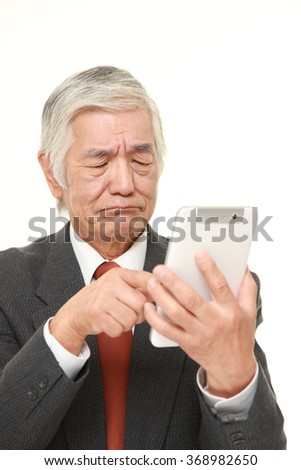 senior Japanese businessman using tablet computer looking confused - stock photo