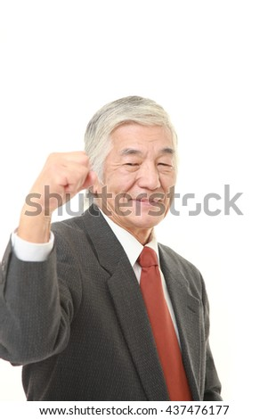 senior Japanese businessman wearing a gray suit in a victory pose