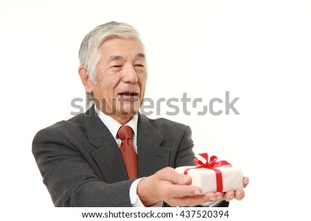 senior Japanese businessman wearing a gray suit offering a gift - stock photo