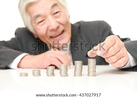 senior Japanese businessman wearing a gray suit  put coins to stack of coins