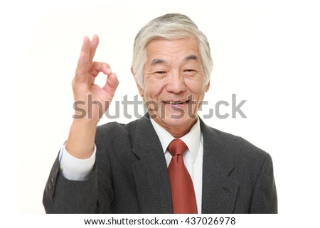 senior Japanese businessman wearing a gray suit showing perfect sign