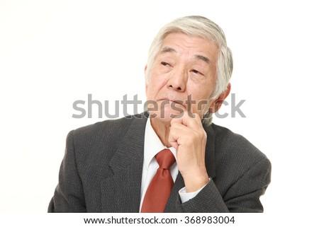 senior Japanese businessman worries about something - stock photo