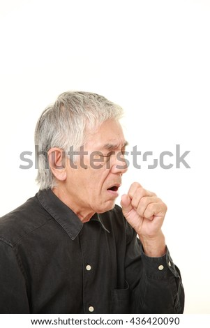 senior Japanese man in a black shirts coughing?