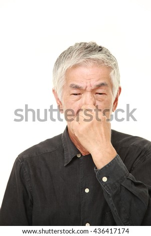 senior Japanese man in a black shirts holding his nose because of a bad smell