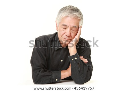 senior Japanese man  in a black shirts sleeping on the table