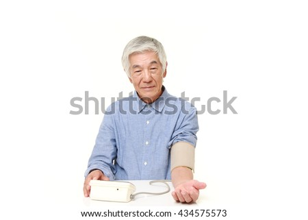 senior Japanese man in a blue shirts checking his blood pressure