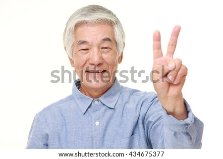 senior Japanese man in a blue shirts showing a victory sign