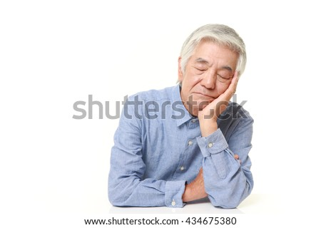 senior Japanese man in a blue shirts sleeping on the table